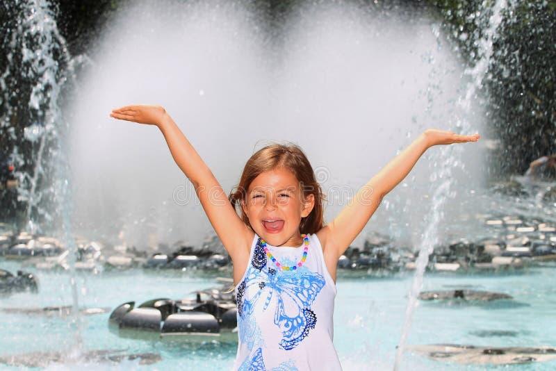 Menina que grita com prazer pela fonte fotografia de stock