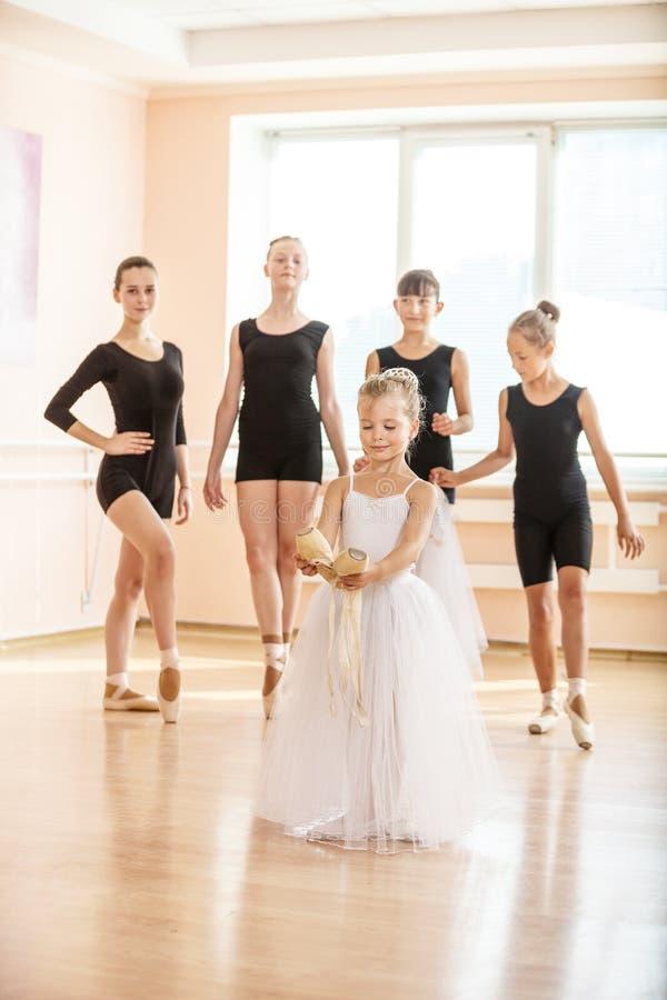 Menina que guarda as sapatas do pointe, estudantes danding do bailado mais velho no fundo foto de stock royalty free