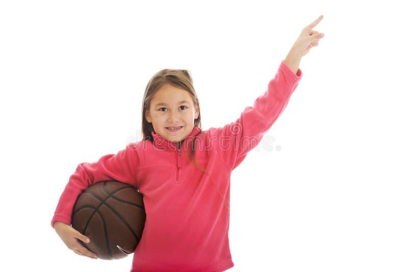 Menina que guarda a bola da cesta imagem de stock