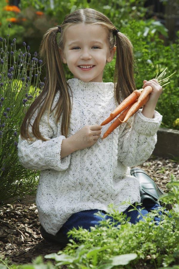 Menina que guarda cenouras no jardim fotos de stock royalty free