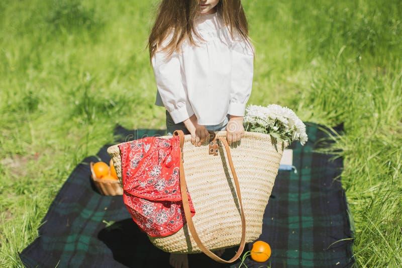Menina que guarda a cesta nas mãos com flores fotografia de stock royalty free