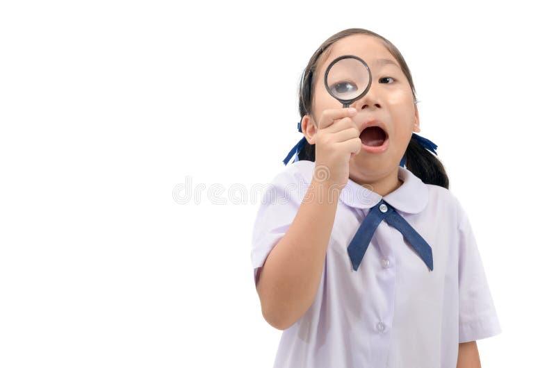 Menina que guarda e que olha através da lupa foto de stock