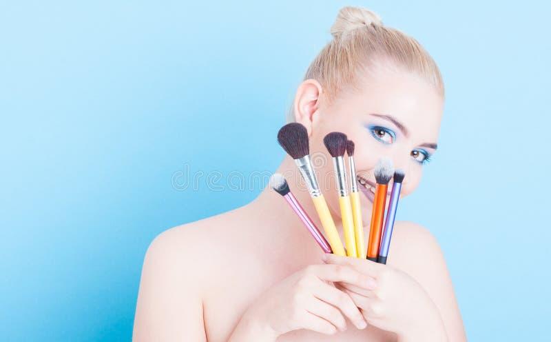 Menina que guarda escovas e sorriso do profissional da composição fotografia de stock royalty free