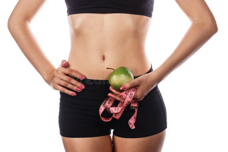 Menina que guarda a fita de medição e a maçã verde fotografia de stock royalty free