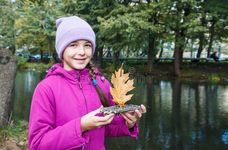 Menina que guarda a jangada pequena feito a mão de madeira do brinquedo imagem de stock royalty free