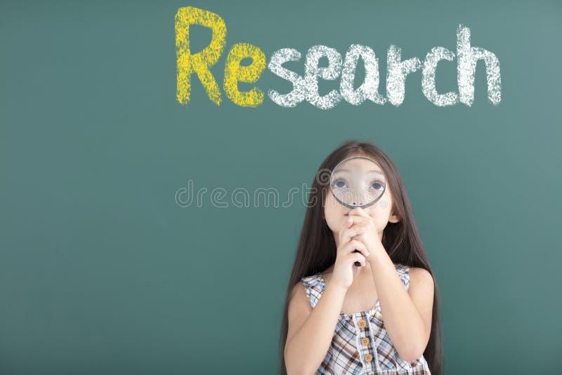 menina que guarda a lupa com conceito da pesquisa imagens de stock royalty free