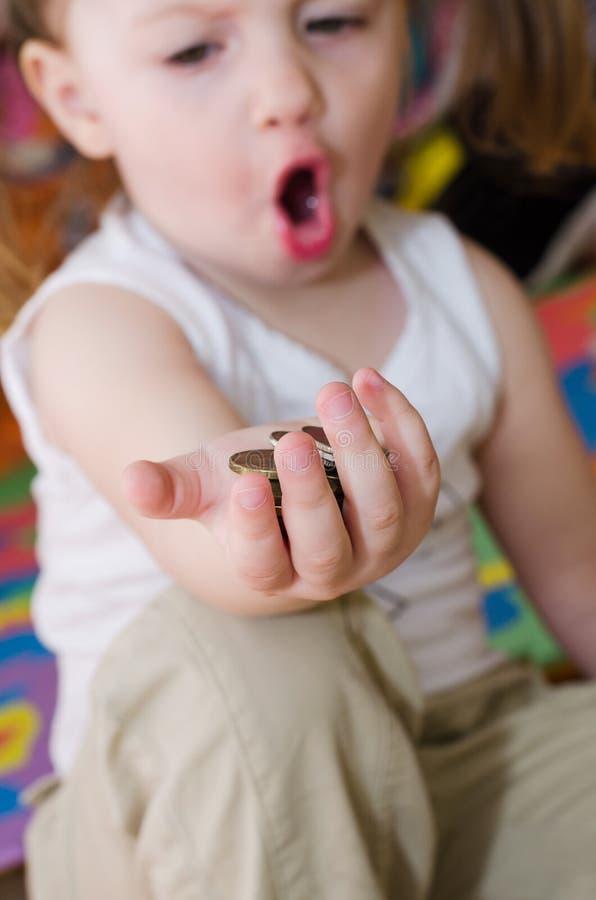 Menina que guarda moedas em sua mão fotografia de stock