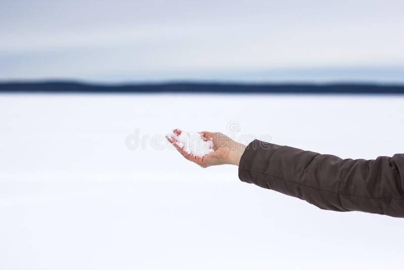 Menina que guarda a neve em sua mão na perspectiva de um lago congelado fotografia de stock