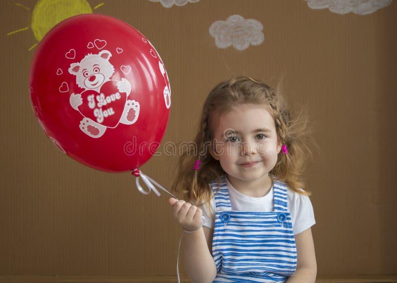Menina que guarda o balão vermelho, sorrindo na câmera foto de stock royalty free