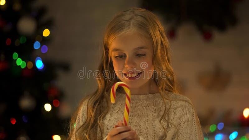 Menina que guarda o bastão de doces saboroso doce, apreciando doces do Natal, infância imagens de stock royalty free