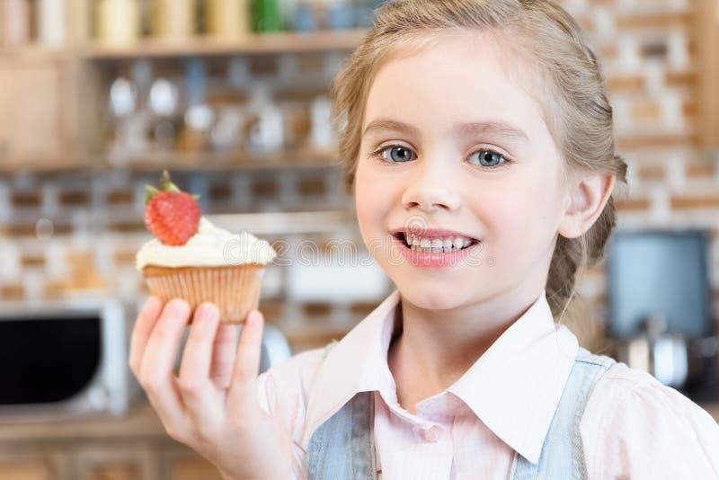 Menina que guarda o bolo caseiro e que sorri na câmera fotos de stock