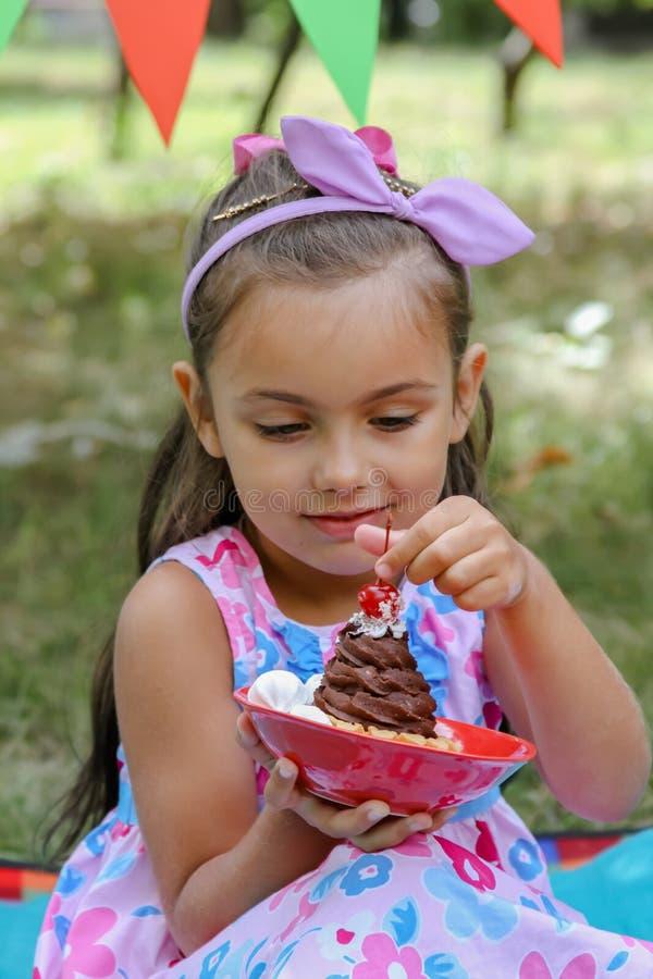 Menina que guarda o bolo delicioso com cereja fotografia de stock royalty free