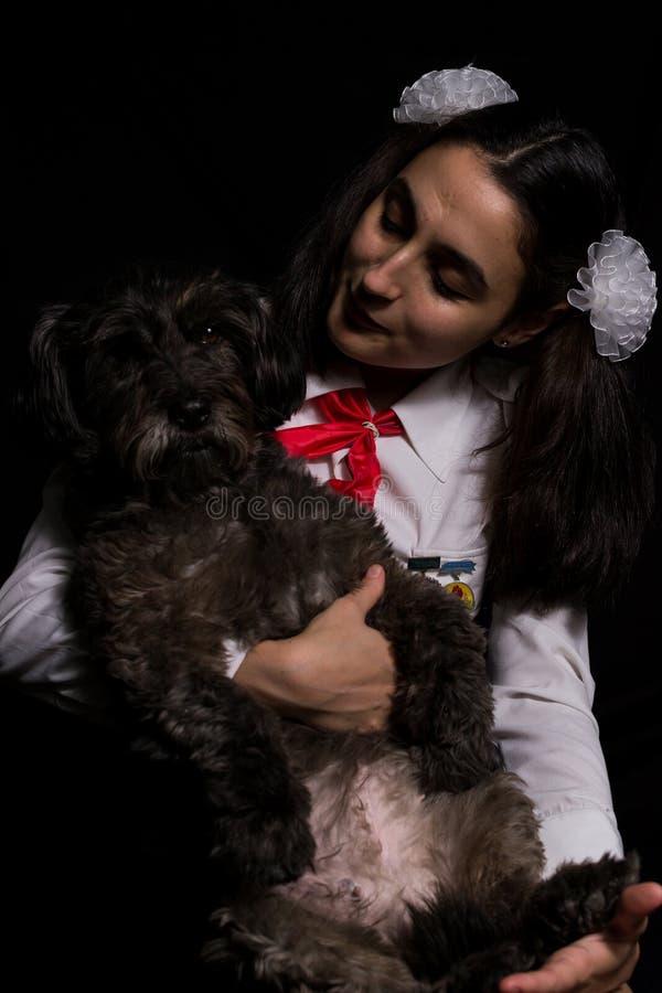 Menina que guarda o cão preto imagens de stock royalty free