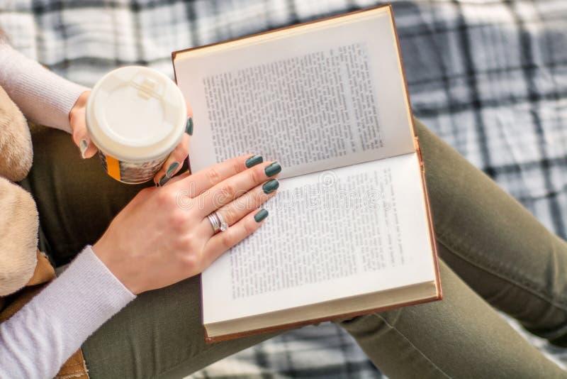 Menina que guarda o copo do livro e de café no pé e na leitura fotografia de stock royalty free