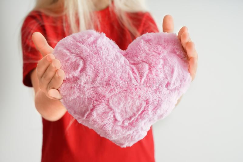 Menina que guarda o descanso coração-dado forma macio no fundo branco, close up fotografia de stock royalty free