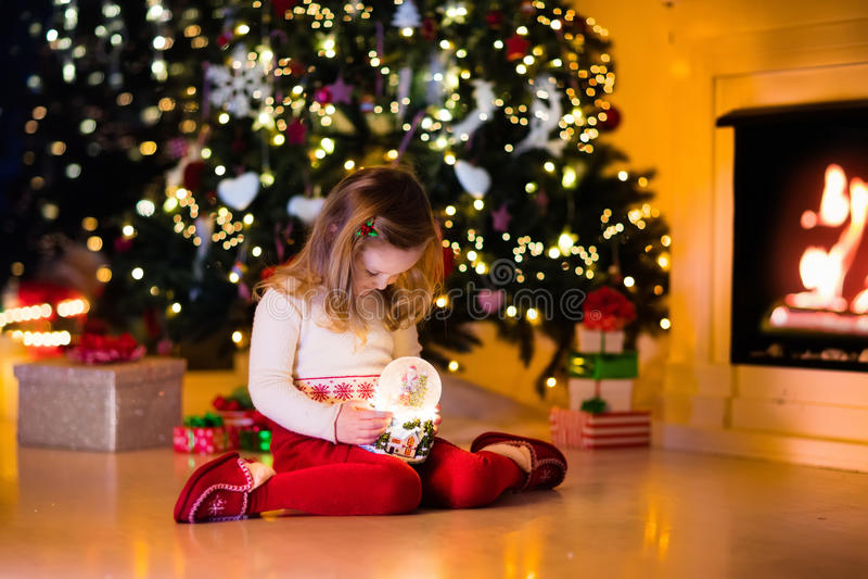 Menina que guarda o globo da neve sob a árvore de Natal foto de stock royalty free