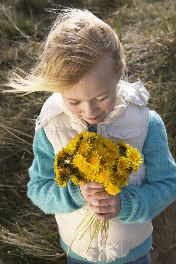 Menina que guarda o grupo de flores fora imagens de stock