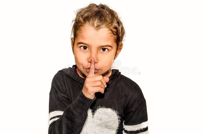 Menina que guarda o indicador em torno da boca Um gesto do silêncio imagem de stock