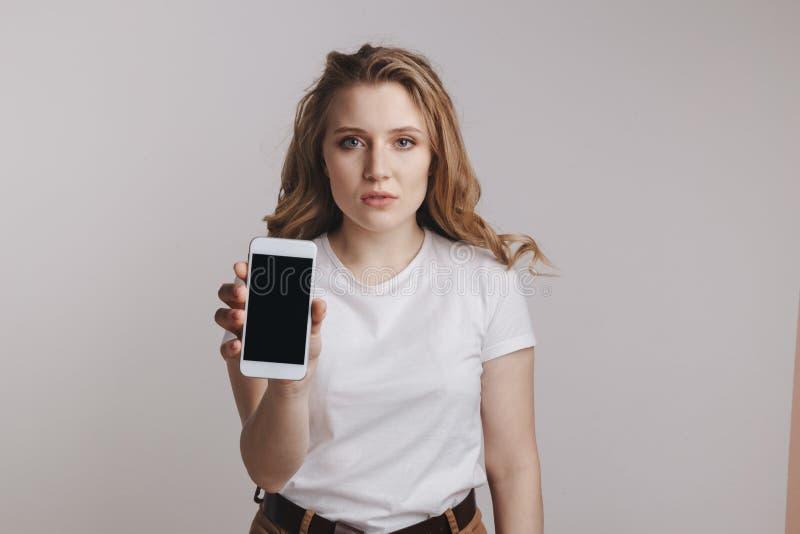 Menina que guarda o iphone branco fotos de stock royalty free