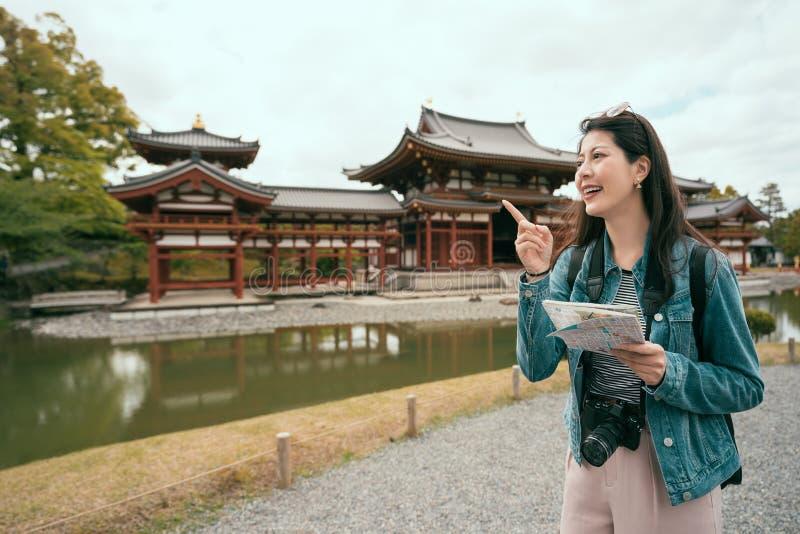 Menina que guarda o mapa de papel que aponta alegremente o céu foto de stock royalty free