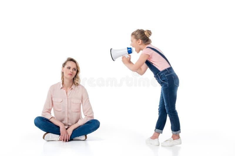 Menina que guarda o megafone e que grita no assento pensativo da mãe fotografia de stock royalty free
