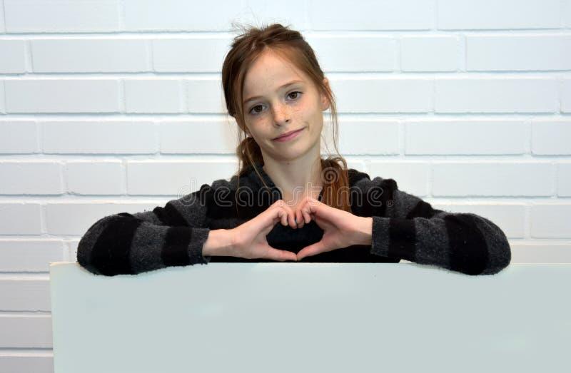 Menina que guarda o quadro de avisos fotografia de stock royalty free