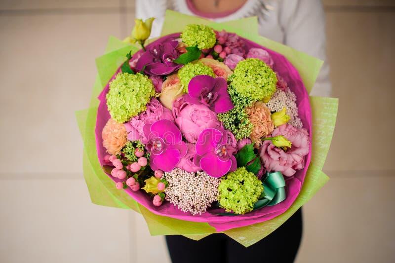 Menina que guarda o ramalhete de flores cor-de-rosa e verdes imagem de stock royalty free