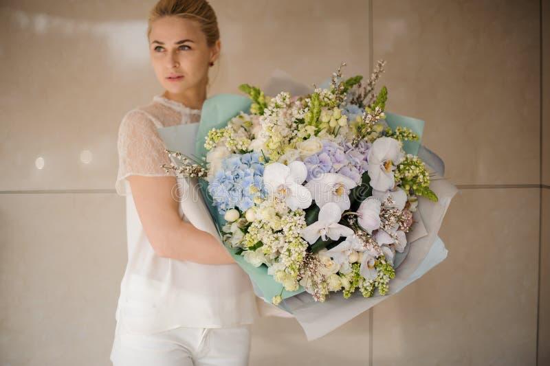 Menina que guarda o ramalhete gigante de flores diferentes imagem de stock