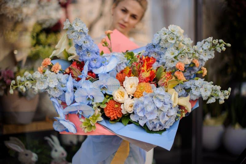 Menina que guarda o ramalhete grande de flores azuis imagem de stock royalty free