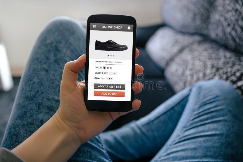 Menina que guarda o telefone esperto com conceito em linha da loja na tela fotografia de stock royalty free