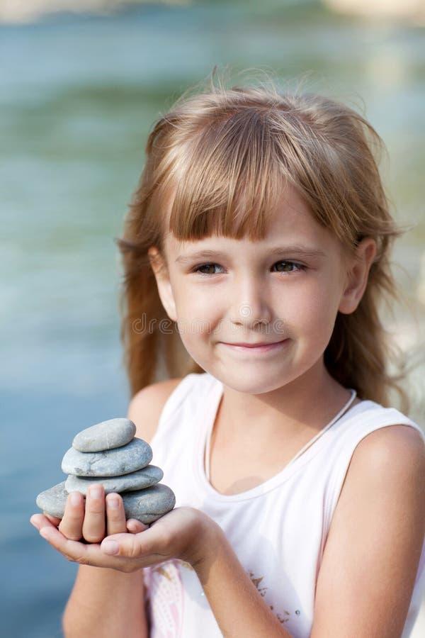 Menina que guarda a pirâmide das pedras foto de stock royalty free