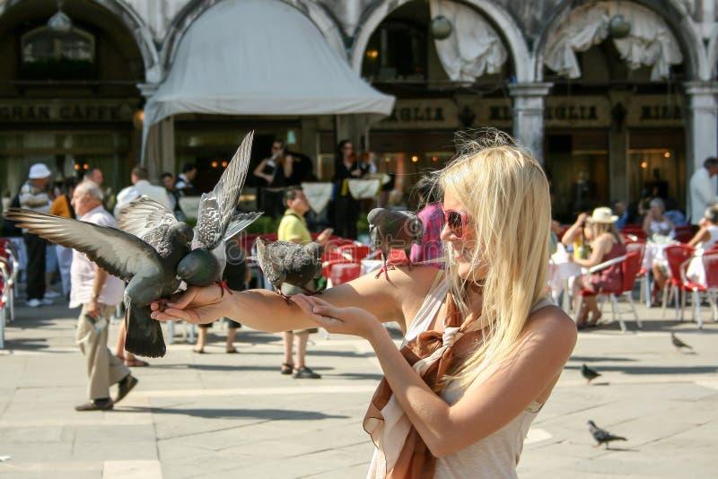 Menina que guarda pombos na praça San Marco Venice Italy Os pombos rivalizaram uma vez gatos como, mascote tradicionais, se não o fotografia de stock royalty free