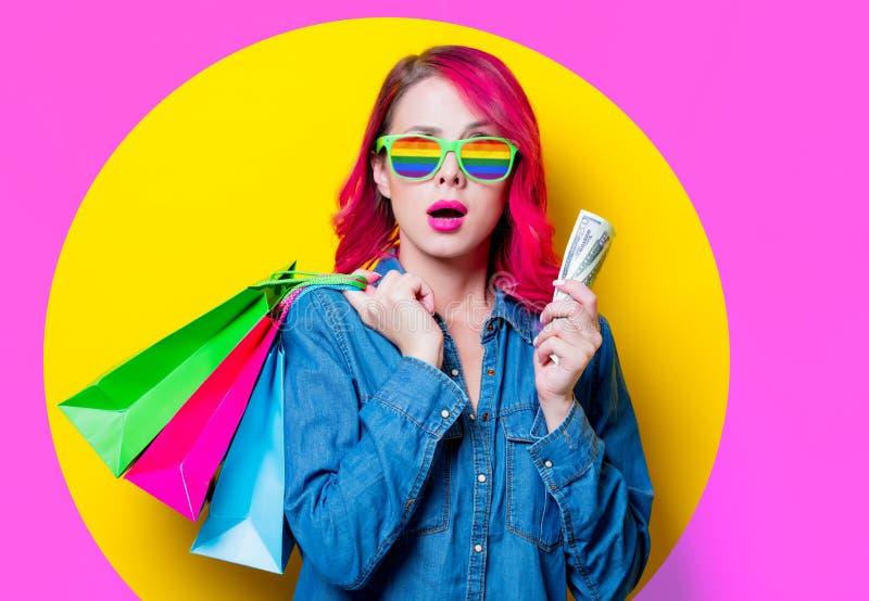 Menina que guarda sacos de compras com dinheiro imagens de stock royalty free