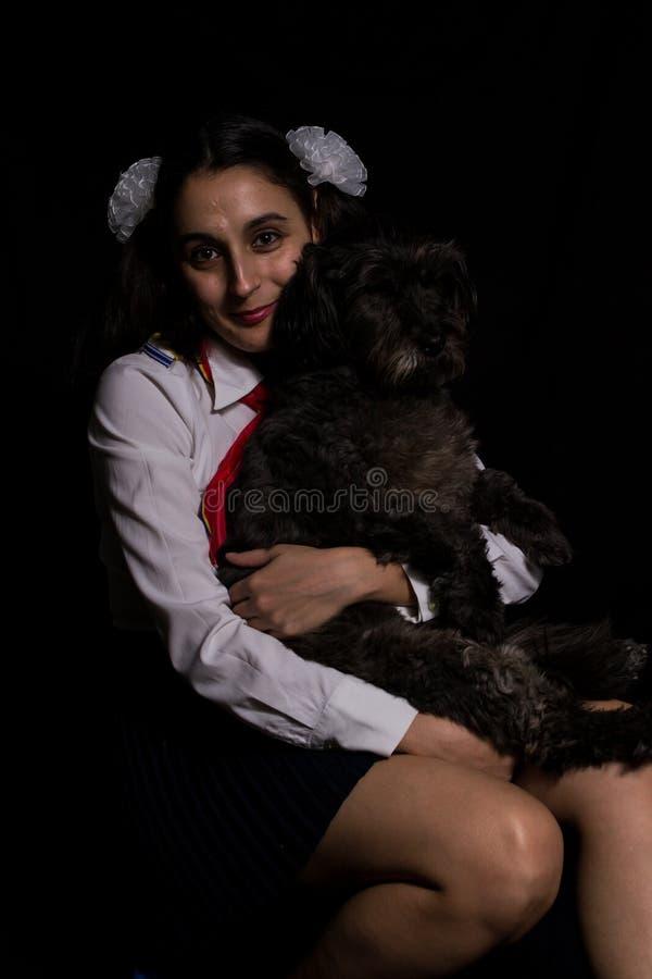 Menina que guarda seu cão preto fotos de stock
