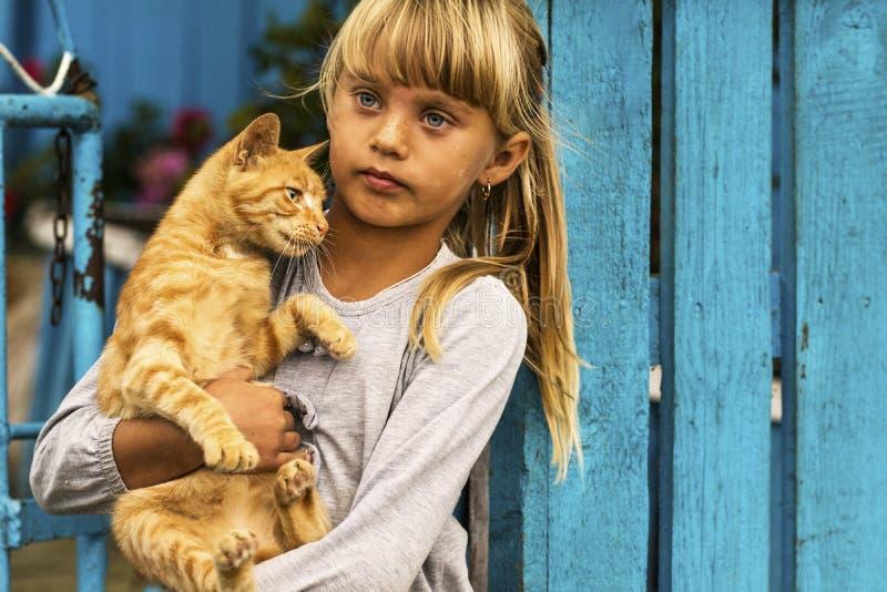 Menina que guarda seu gato fotografia de stock