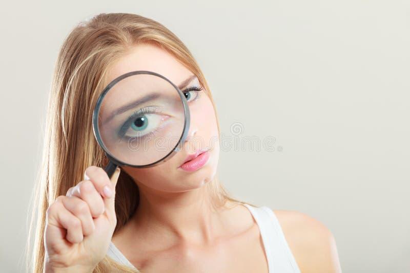 Menina que guarda sobre a lupa da lupa do olho imagem de stock