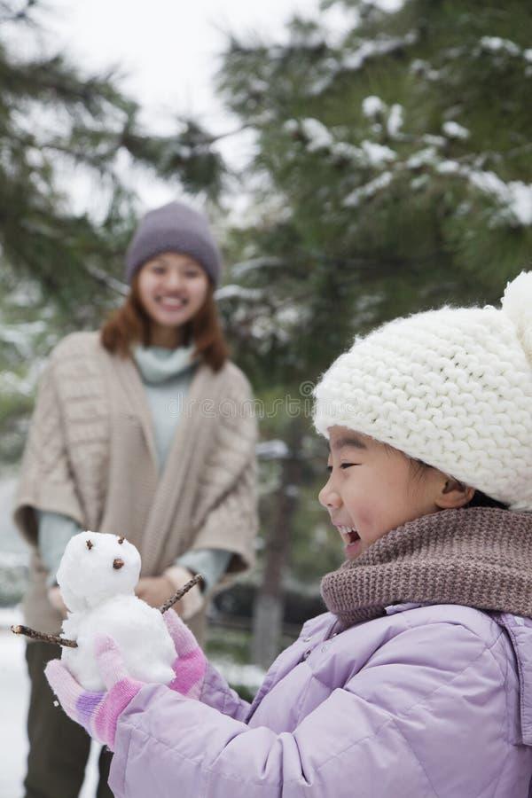 Menina que guarda um boneco de neve em um parque com mãe imagens de stock royalty free