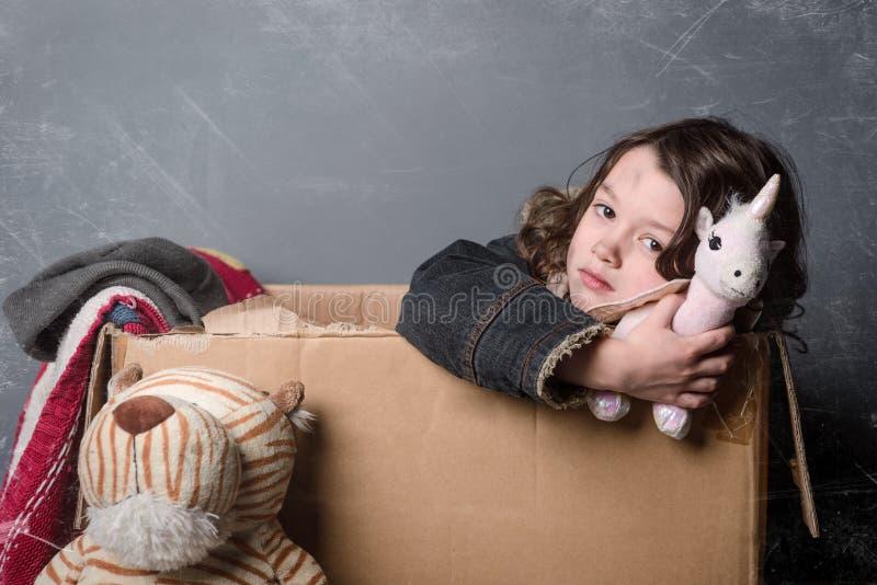 Menina que guarda um brinquedo usado foto de stock