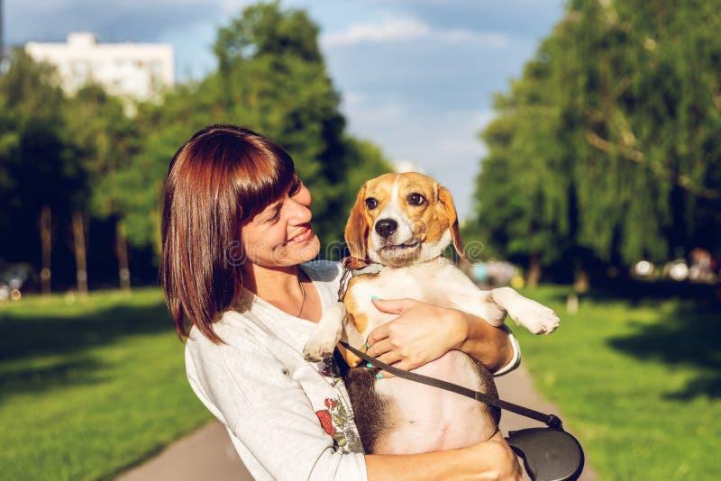 Menina que guarda um cão em seus braços no fundo da natureza em horas de verão Foto do estilo de vida imagens de stock royalty free