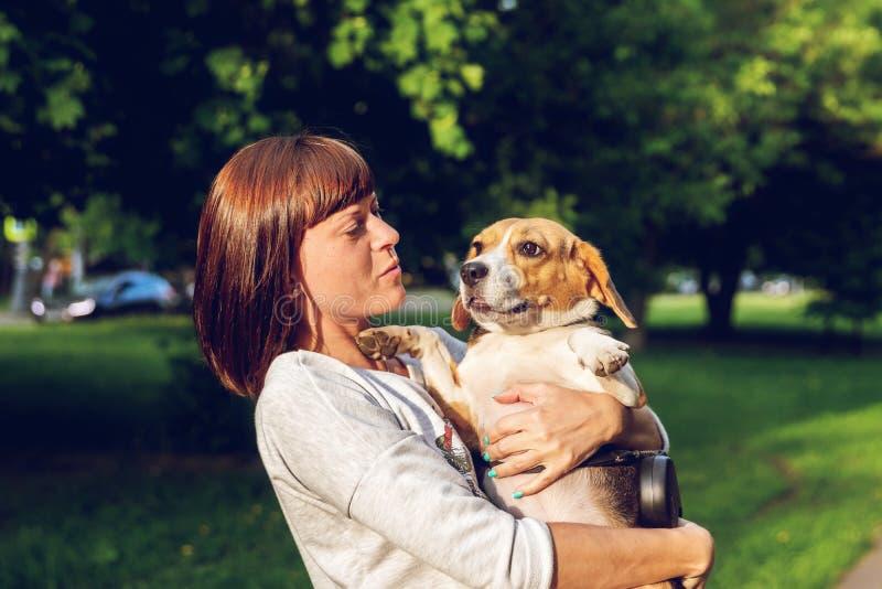 Menina que guarda um cão em seus braços no fundo da natureza em horas de verão Foto do estilo de vida fotografia de stock royalty free