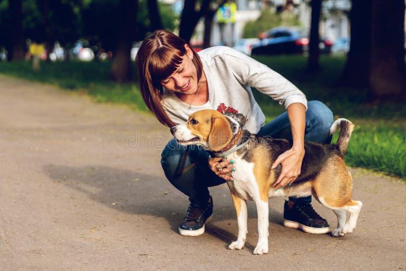 Menina que guarda um cão em seus braços no fundo da natureza em horas de verão Foto do estilo de vida foto de stock royalty free