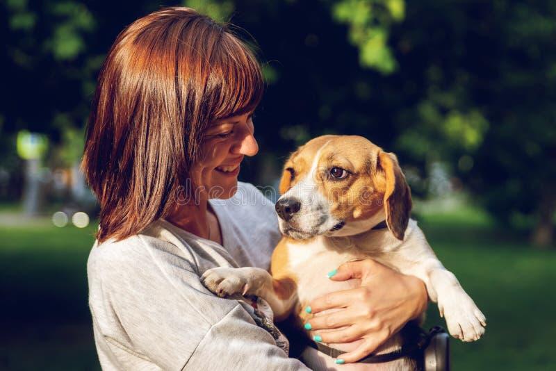Menina que guarda um cão em seus braços no fundo da natureza em horas de verão Foto do estilo de vida fotos de stock royalty free