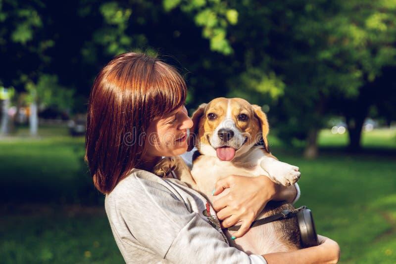 Menina que guarda um cão em seus braços no fundo da natureza em horas de verão Foto do estilo de vida foto de stock