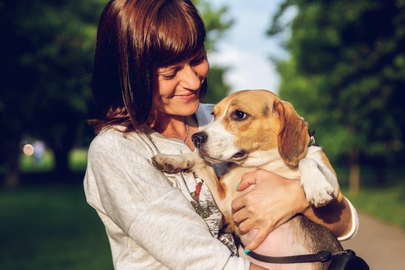 Menina que guarda um cão em seus braços no fundo da natureza em horas de verão Foto do estilo de vida imagem de stock