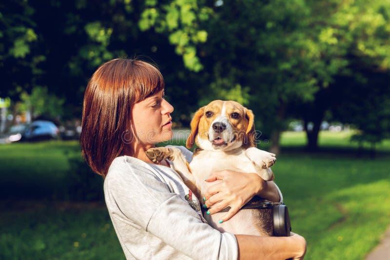 Menina que guarda um cão em seus braços no fundo da natureza em horas de verão Foto do estilo de vida fotografia de stock