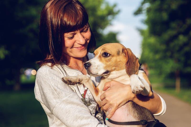Menina que guarda um cão em seus braços no fundo da natureza em horas de verão Foto do estilo de vida imagens de stock