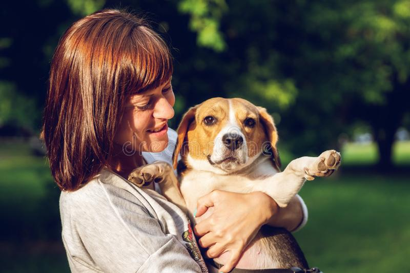 Menina que guarda um cão em seus braços no fundo da natureza em horas de verão Foto do estilo de vida fotos de stock