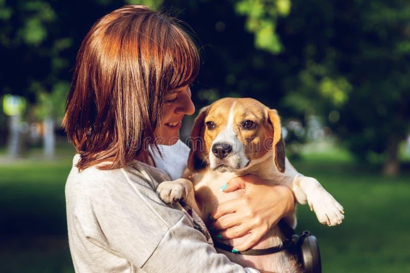 Menina que guarda um cão em seus braços no fundo da natureza em horas de verão Foto do estilo de vida imagem de stock royalty free