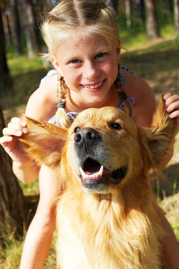 Menina que guarda um cão engraçado pelas orelhas fotografia de stock royalty free