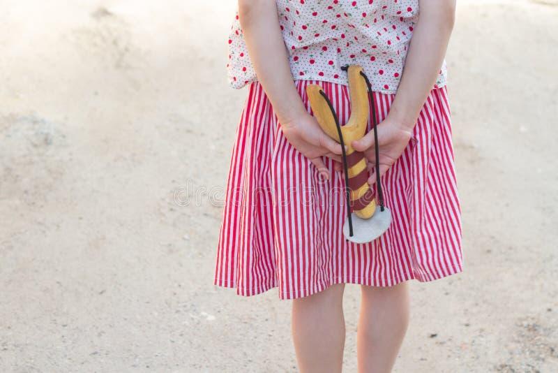 Menina que guarda um estilingue em suas mãos foto de stock
